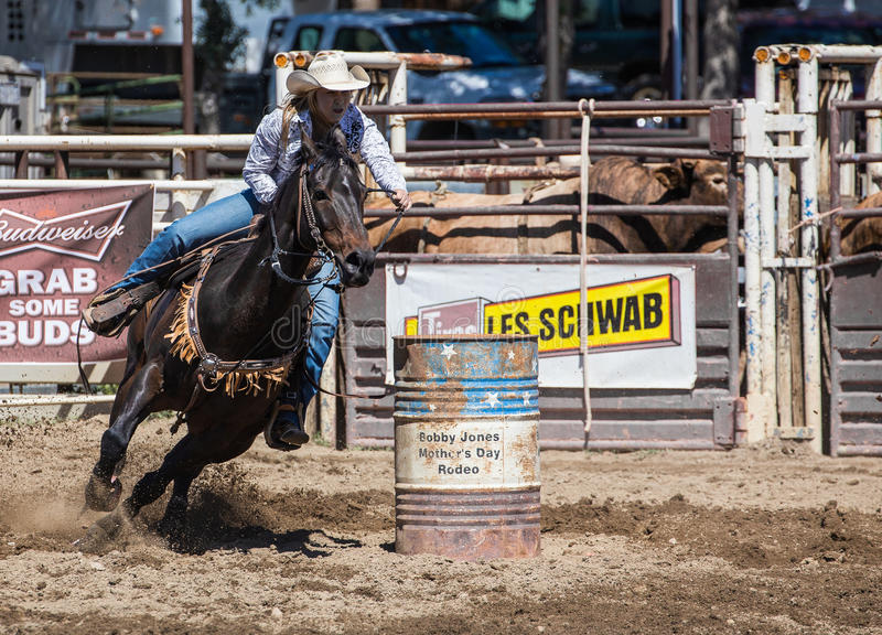 Moving to the Next One. A cowgirl clears a barrel during a barrel racing event. The rodeo in Cottonwood, California is a popular event on Mother's Day weekend in royalty free stock photo