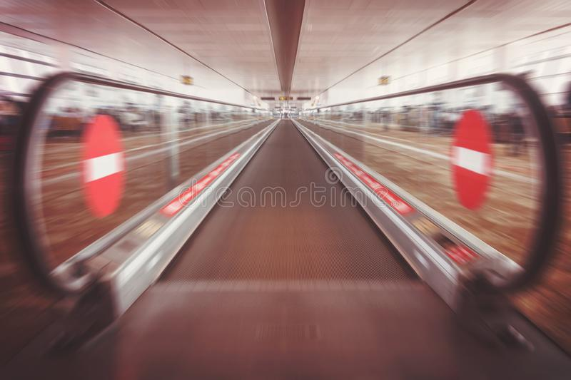 Moving waklway in the airport terminal, travel concept. Straight flat escalator. motion effect. entry banned a badge of. there is no way royalty free stock images