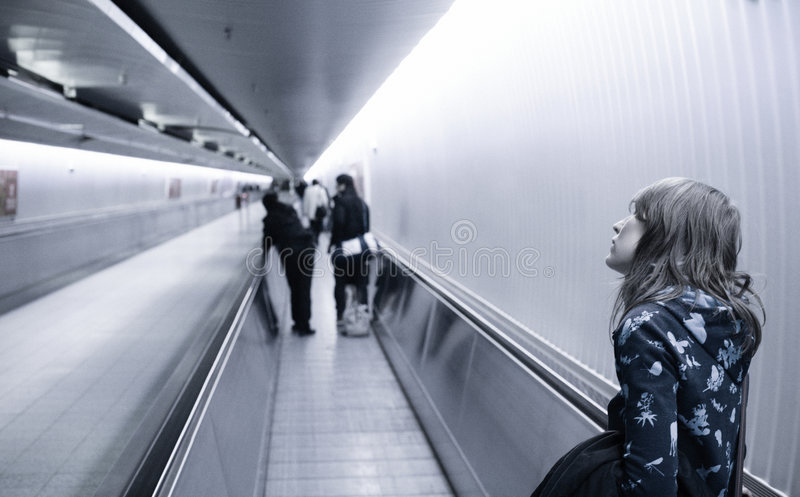 Moving walkway. Girl on moving walkway escalator in airport royalty free stock images