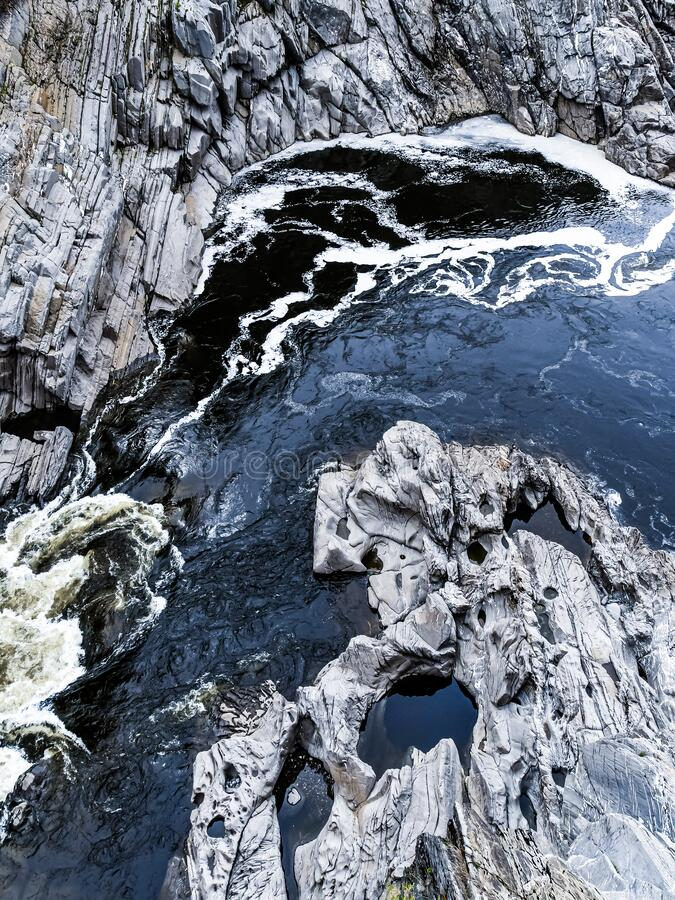 Moving Water through Rock Walls Creating Art. View of  the Saint John River below the Grand Falls waterfall in New Brunswick, Canada, as it flows over eroding stock photography