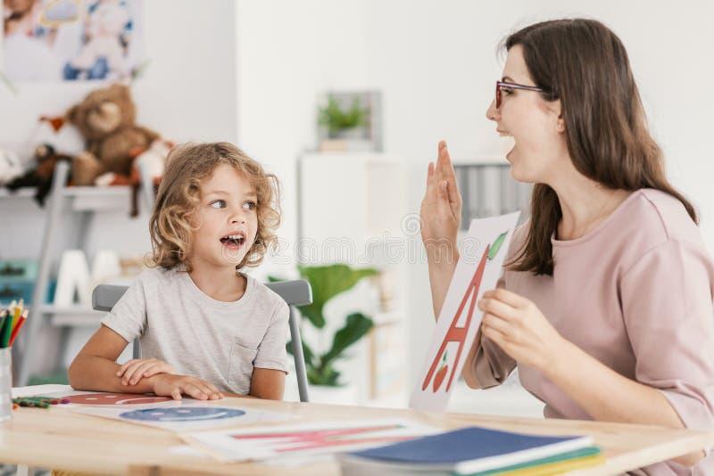 Mowa terapeuta nauczania listu wymawianie młoda chłopiec wewnątrz fotografia royalty free