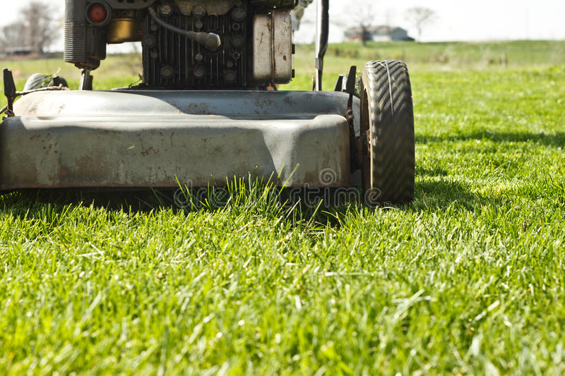 Mower Finish Lawn. Push mower stopped in front of a small patch of grass in a finished lawn royalty free stock image