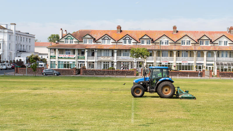 Mowing Grass. A corporation tractor being used to mow the grass in Paignton, Devon, United Kingdom stock photo