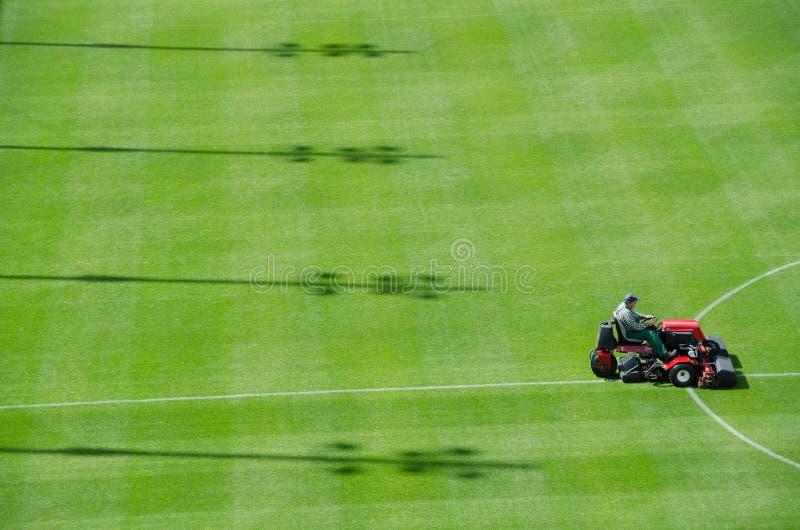 Mowing grass. LUBIN, POLAND - AUGUST 10: Stadium workers trim football field grass at Zaglebie Lubin Stadium before match Polish Premier League on August 10 royalty free stock photos