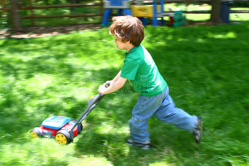Mowing the lawn. Small child pretending to mow the lawn stock photography