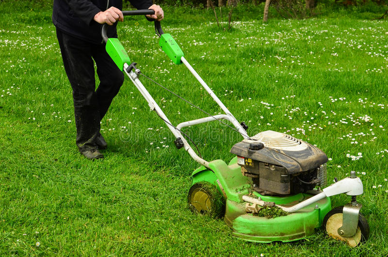 Mowing the lawn. Gardener mowing green grass lawn with push mower stock photo