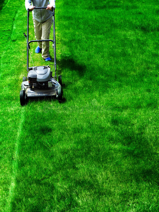Mowing Lawn Grass. Young Girl Mowing green grass lawn with push mower stock photography