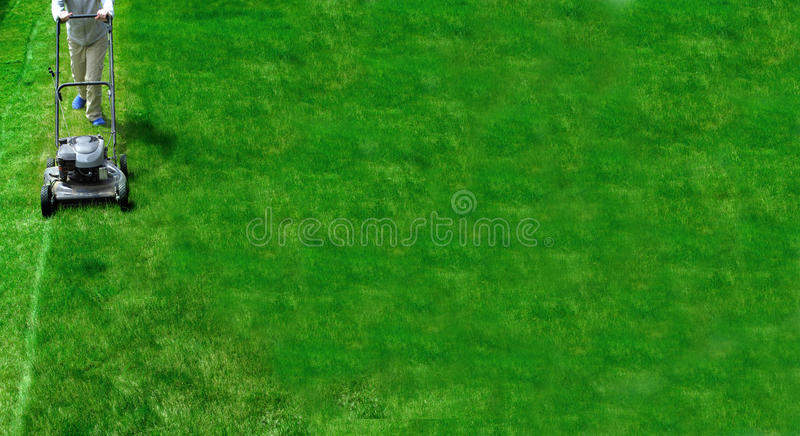 Mowing Lawn Grass. Young Girl Mowing green grass lawn with push mower royalty free stock photography
