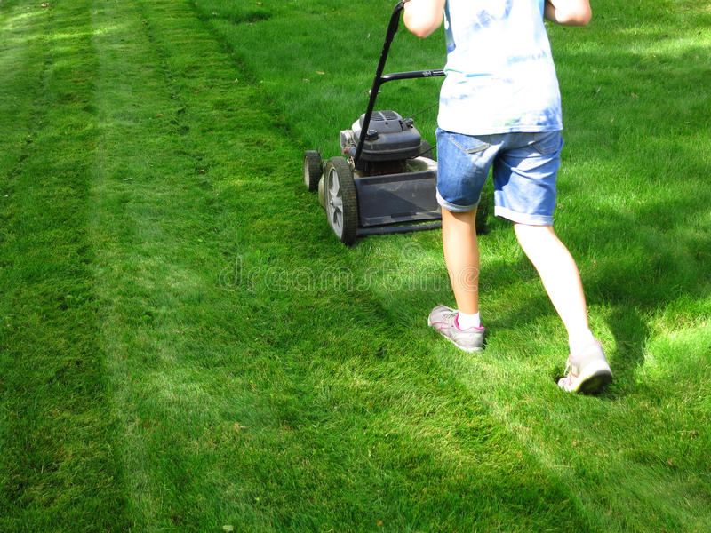 Mowing Lawn Grass. Young Girl Mowing green grass lawn with push lawn mower royalty free stock image