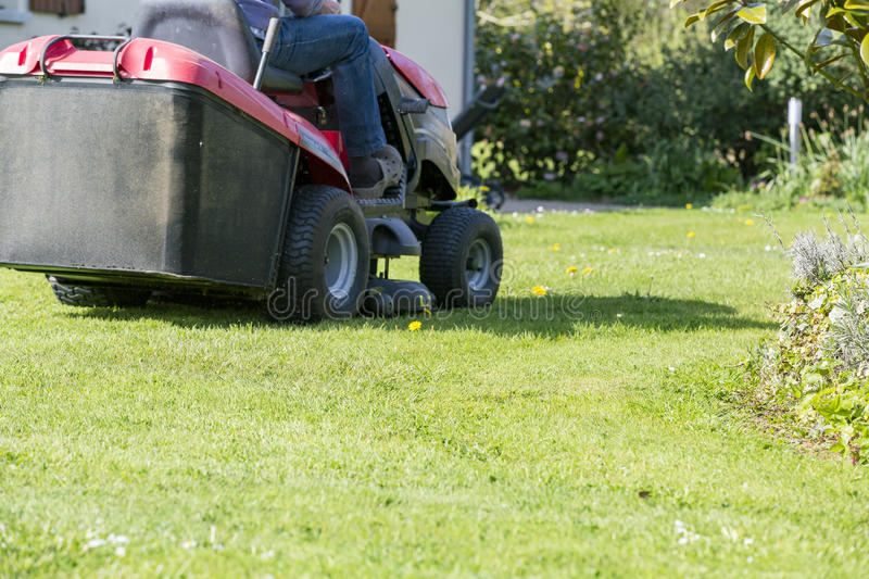 Mowing the lawn with tractor stock images