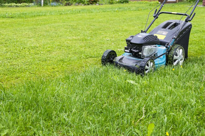 Mowing lawns. Lawn mower on green grass. mower grass equipment. mowing gardener care work tool close up view sunny day stock images