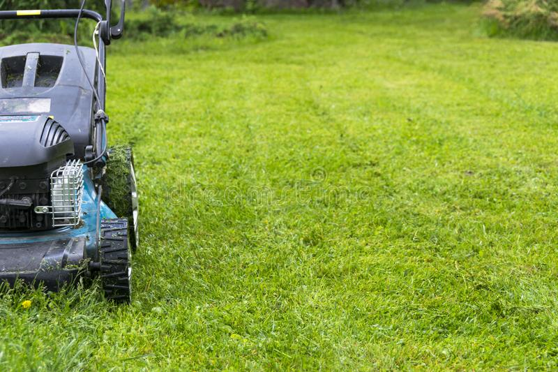 Mowing lawns. Lawn mower on green grass. mower grass equipment. mowing gardener care work tool close up view sunny day. Mowing lawns. Lawn mower on green grass stock image