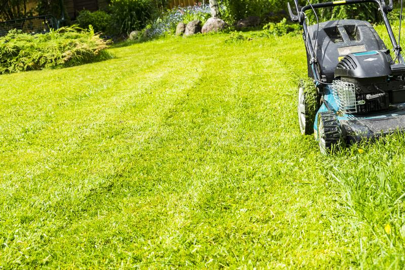 Mowing lawns, Lawn mower on green grass, mower grass equipment, mowing gardener care work tool, close up view, sunny day. stock photography