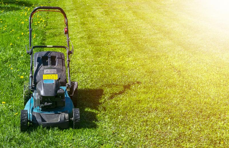 Mowing lawns, Lawn mower on green grass, mower grass equipment, mowing gardener care work tool, close up view, sunny day. Soft lig stock image