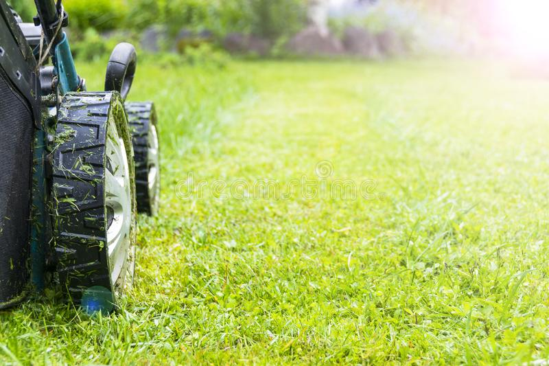 Mowing lawns, Lawn mower on green grass, mower grass equipment, mowing gardener care work tool, close up view, sunny day. Soft royalty free stock photography