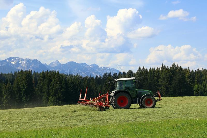 Mowing in summer on a field in Bavaria royalty free stock images