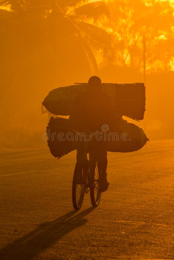 A Mozambican cyclist carrying large bags of coal to market stock image