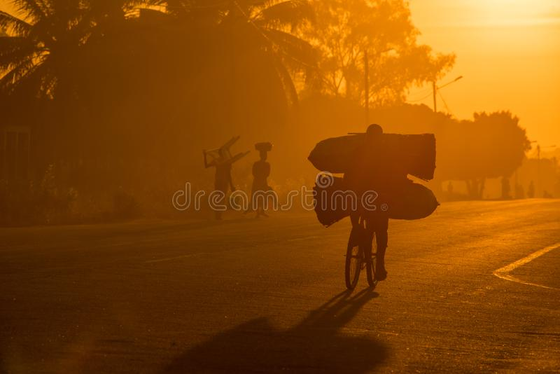 A Mozambican cyclist carrying large bags of coal to market at sunrise stock images