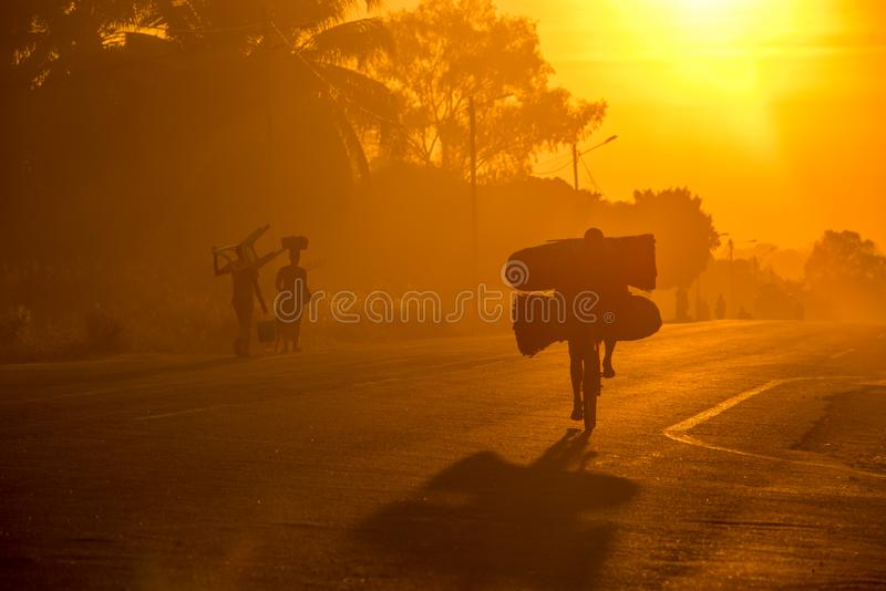 A Mozambican cyclist carrying large bags of coal to market at sunrise stock image