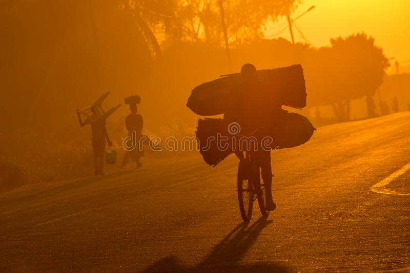 A Mozambican cyclist carrying large bags of coal to market at sunrise stock photos