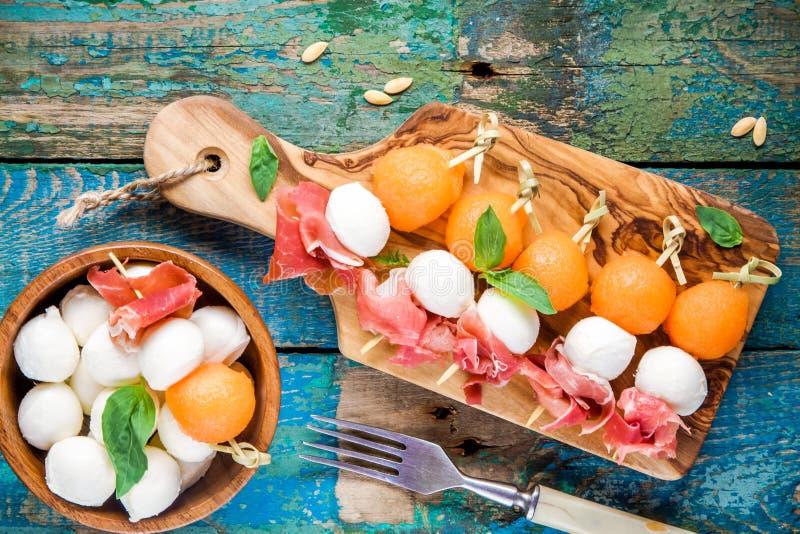 Mozarella en prosciutto met meloen canapes met basilicum op een scherpe raad stock afbeeldingen