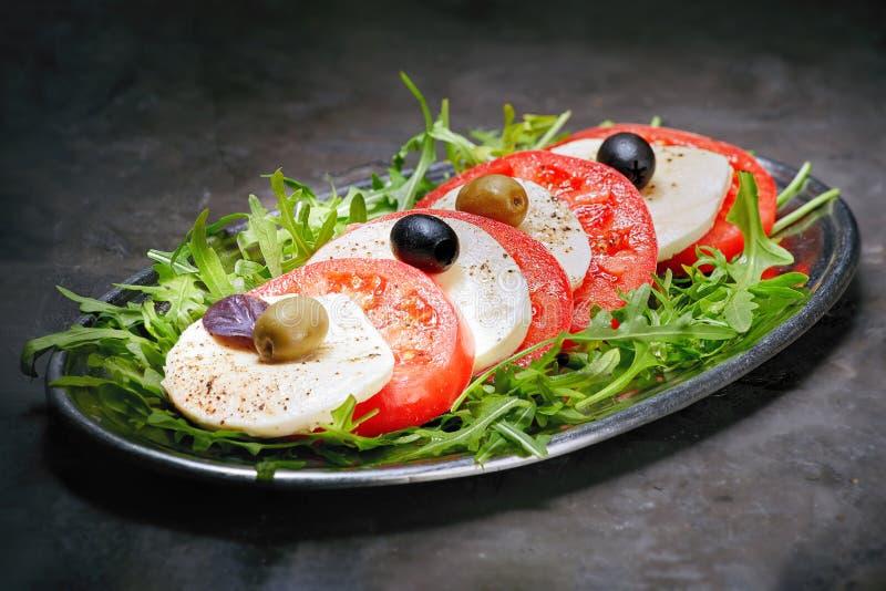 Mozarella met gesneden tomaten, Basilicum en olijven stock foto