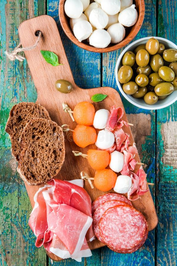 Mozarella, prosciutto, meloen canapes met salami, olijven en brood stock foto's