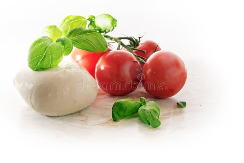 Mozarella, tomaten en basilicumkruid, Italiaanse caprese, op een licht stock fotografie