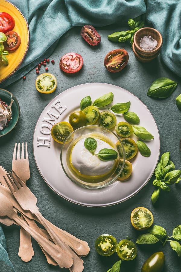 Mozarellakaas in kom met olijfolie, groene tomaten en basilicumbladeren op witte plaat met bestek, hoogste mening stock fotografie