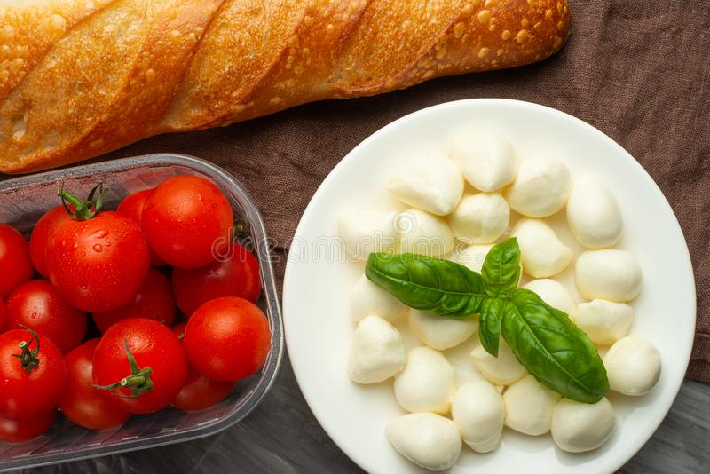 Mozzarella with basil leaves - fresh ingredients for Bruschetta, with cherry tomatoes and French baguette royalty free stock image