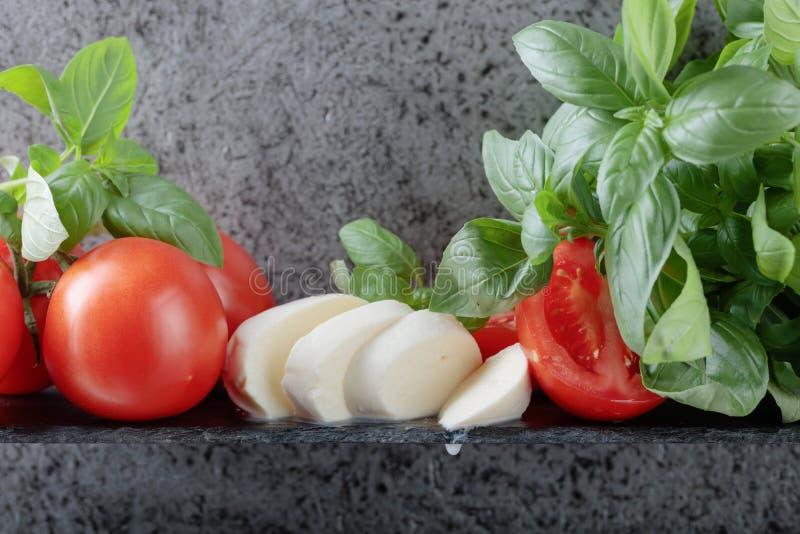 Mozzarella with basil and tomatoes . Mozzarella with basil and tomatoes on a background of old grey wall. Copy space for your text stock photos