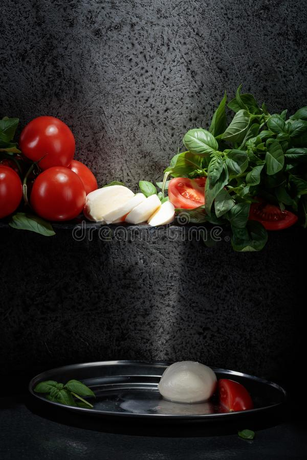 Mozzarella with basil and tomatoes . Mozzarella with basil and tomatoes on a background of old grey wall. Copy space for your text royalty free stock image