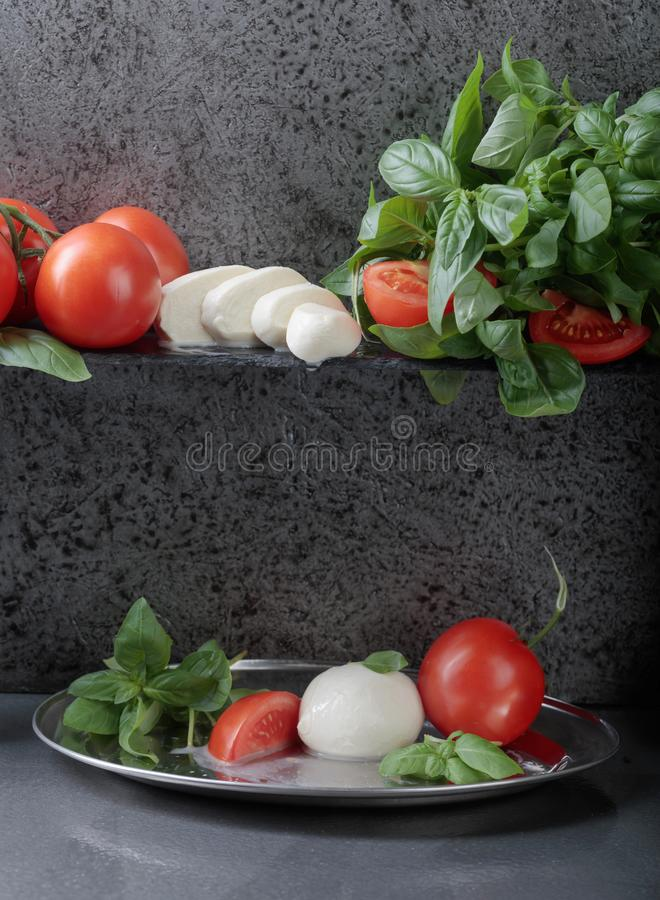 Mozzarella with basil and tomatoes . Mozzarella with basil and tomatoes on a background of old grey wall. Copy space for your text royalty free stock photos