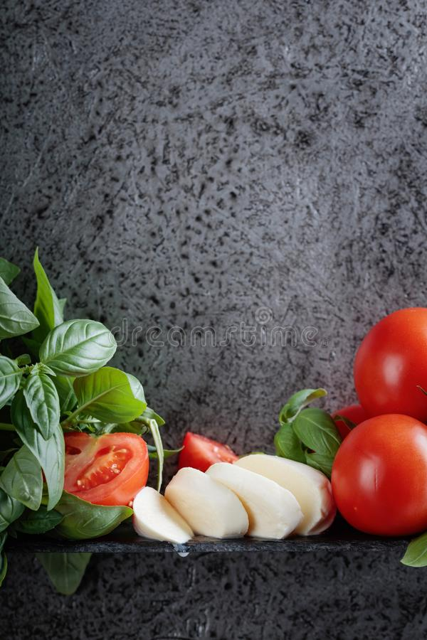 Mozzarella with basil and tomatoes . Mozzarella with basil and tomatoes on a background of old grey wall. Copy space for your text stock images