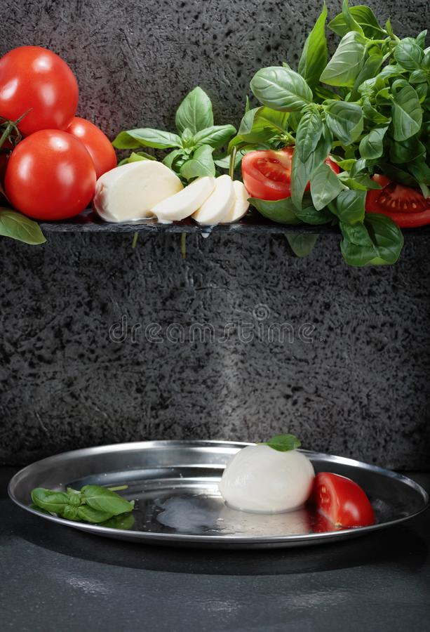 Mozzarella with basil and tomatoes. On a background of old grey wall. Copy space for your text stock photo