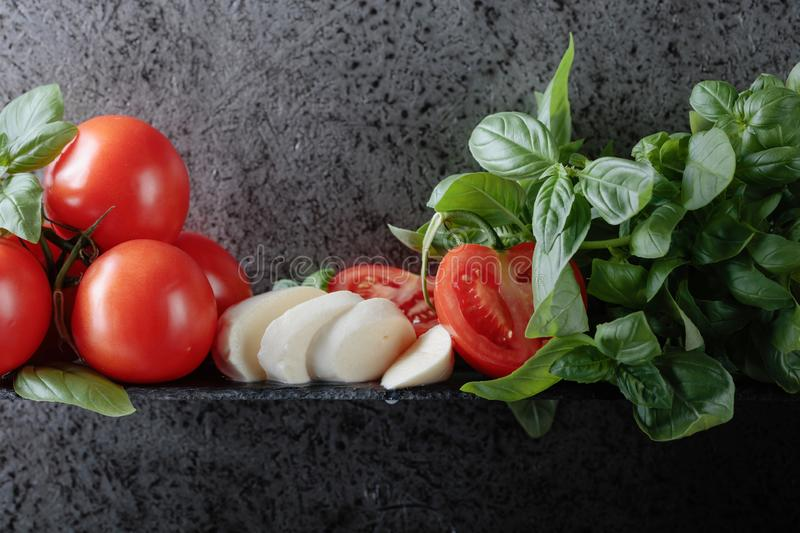 Mozzarella with basil and tomatoes. On a background of old grey wall. Copy space for your text royalty free stock images