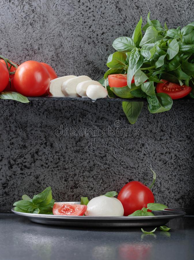 Mozzarella with basil and tomatoes . Mozzarella with basil and tomatoes on a background of old grey wall. Copy space for your text stock image