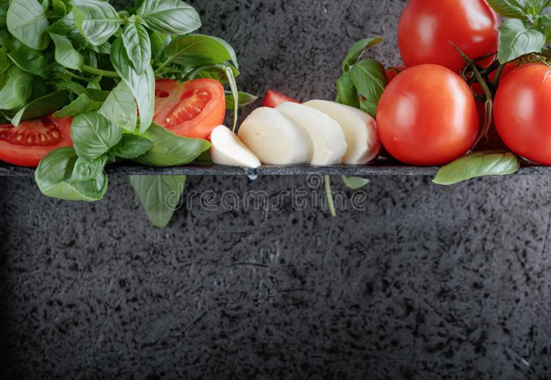 Mozzarella with basil and tomatoes . Mozzarella with basil and tomatoes on a background of old grey wall. Copy space for your text royalty free stock photography