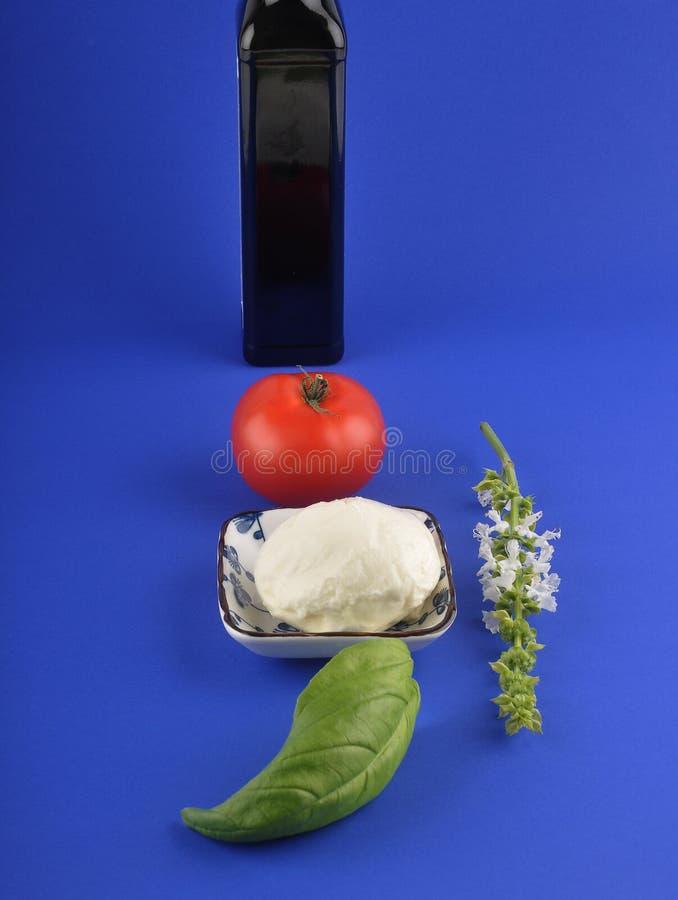 Mozzarella, basilika, olivolja och tomat på blått arkivbilder