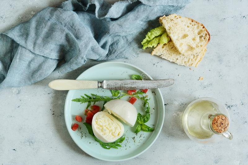 Mozzarella buffalo cheese on a dinner plate with tomato salsa leaves of arugula and basil with olive oil on a gray background. royalty free stock photos