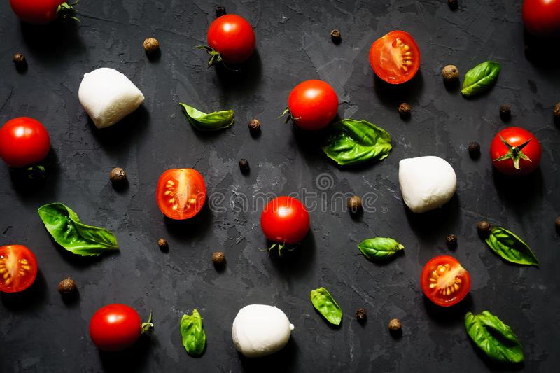 Mozzarella cheese balls with fresh basil leaves and cherry tomatoes,  ingredients for Italian Caprese salad, on a black background royalty free stock photography