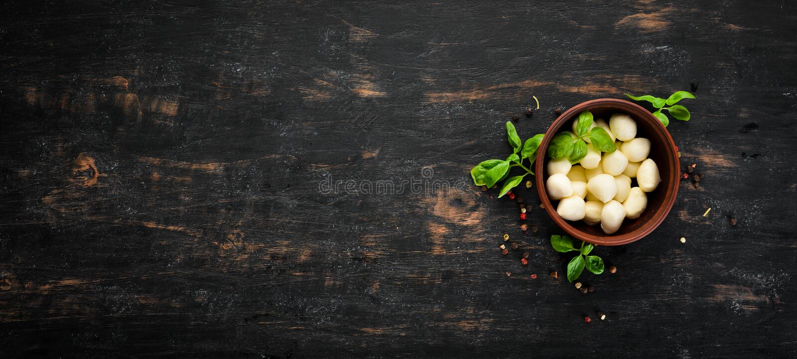 Mozzarella cheese in a clay plate. Top view. On a wooden background. Free copy space stock images