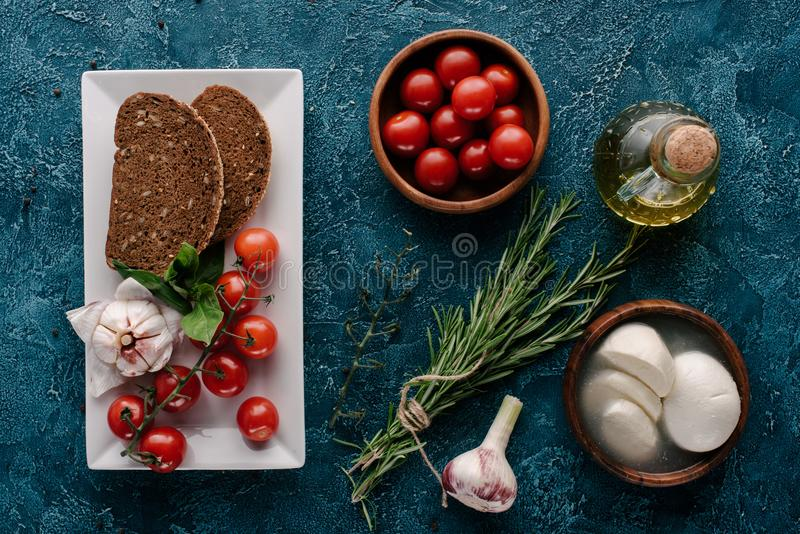 Mozzarella cheese and tomatoes on dark blue table with bread. And herbs stock image