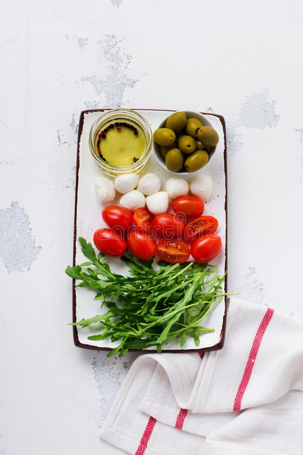 Mozzarella, cherry tomatoes and arugula served in white ceramic rectangular plates with olive oil over grey texture background. royalty free stock photos