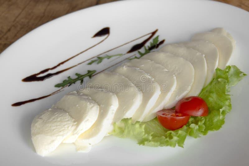 Mozzarella con el tomate de cereza, la ensalada verde y la preparación en una placa blanca en un fondo de madera foto de archivo