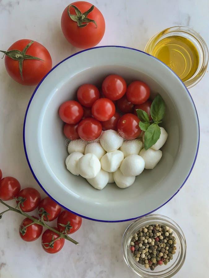 Mozzarella, czereśniowi pomidory i świeży basil, - składniki dla caprese sałatki obrazy royalty free