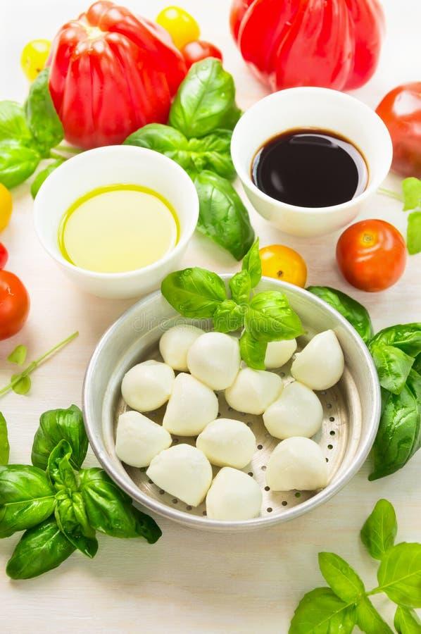Mozzarella in der Schüssel mit Basilikumblättern, Öl, Tomaten und Balsamico-Essig, italienische Lebensmittelinhaltsstoffe stockbilder