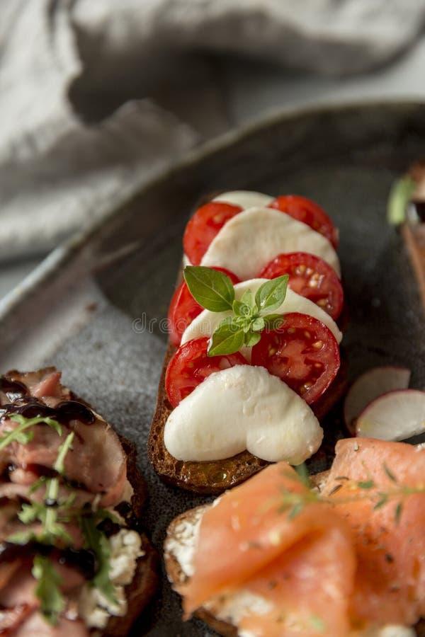Mozzarella et tomates et tapas de basilic photographie stock