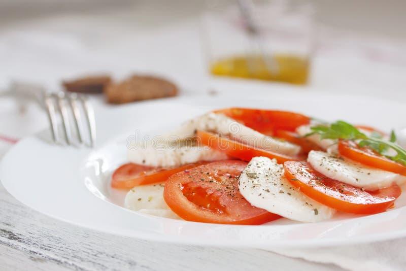 Mozzarella med tomater, italienska örter och rucola på en vit platta på en tabell royaltyfria foton