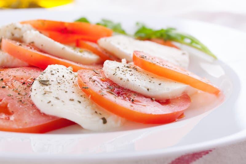Mozzarella med tomater, italienska örter och rucola på en vit platta på en tabell arkivfoton